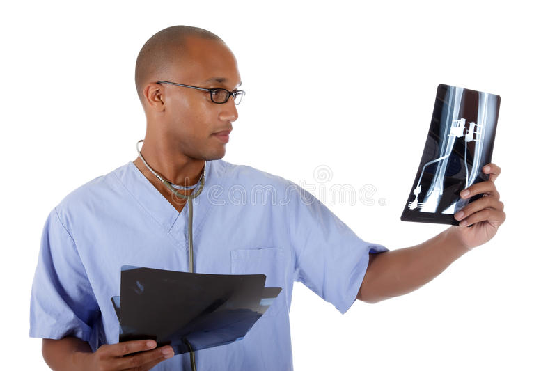 Young successful African American man doctor, xray. Young successful African American man doctor examining x-ray photos. Studio shot. White background royalty free stock photos