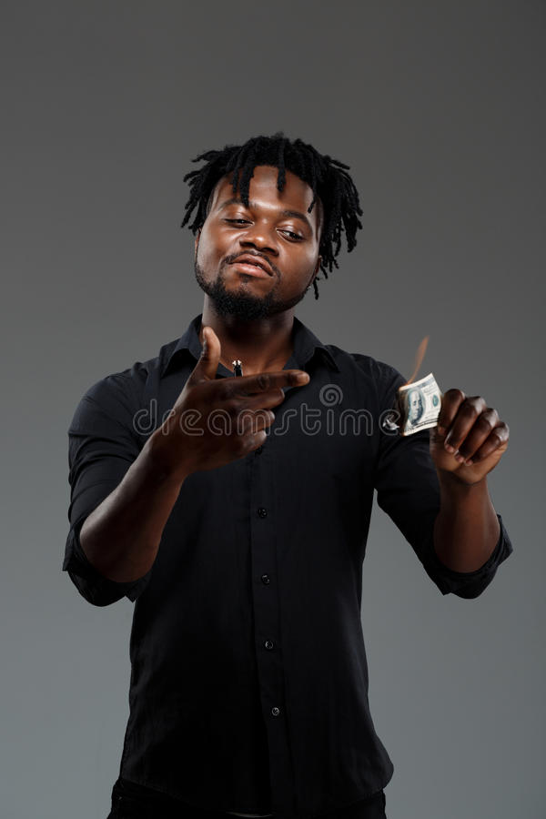Young successful african businessman burning money over dark background. stock photo