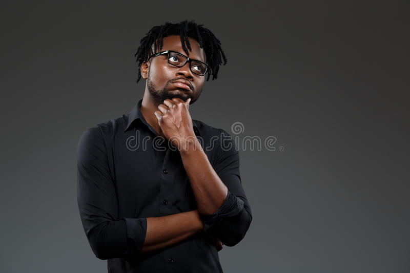 Young successful african businessman in glasses posing over dark background. stock photo