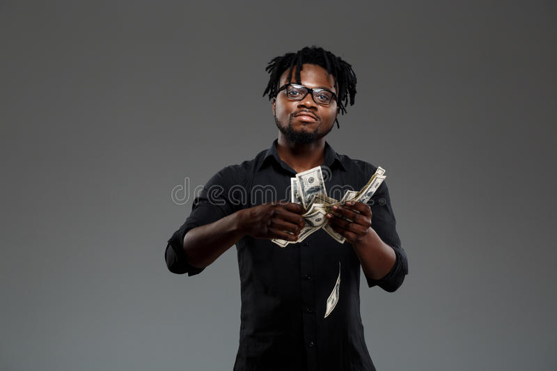Young successful african businessman throwing money over dark background. stock photo