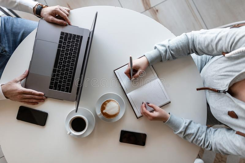 Young successful business executive sits with a laptop and interviews a girl manager in an office. Business meeting men and women royalty free stock photo
