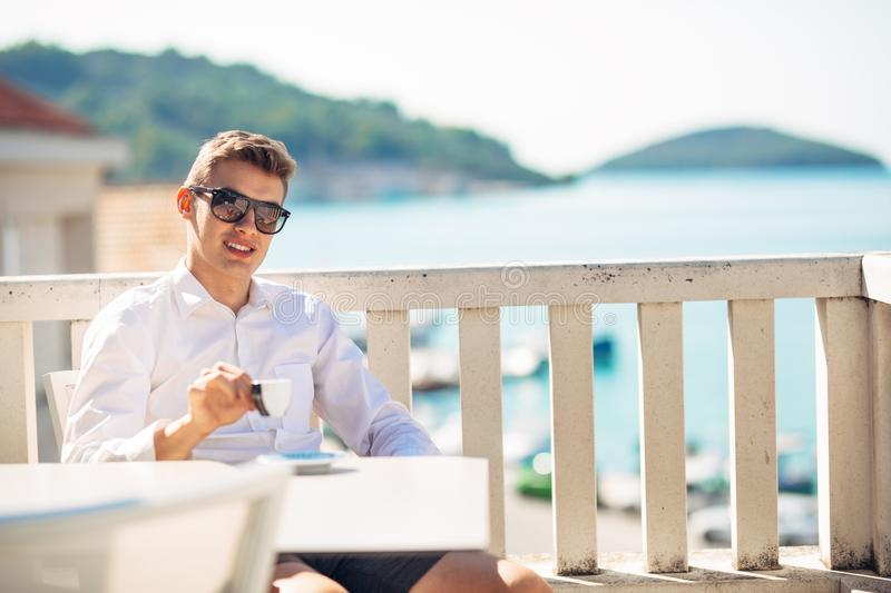Young successful business man enjoying espresso coffee beverage in sunny marine panoramic cafe. royalty free stock image