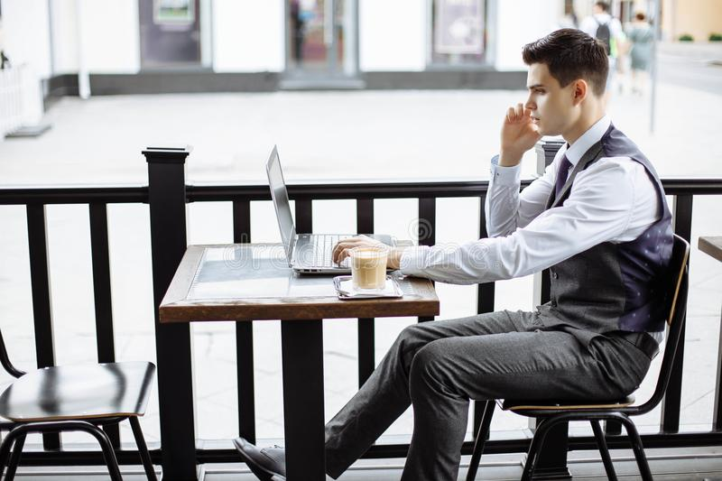 Young successful business man sitting in outdoor urban cafe with laptop and talking on phone royalty free stock photo