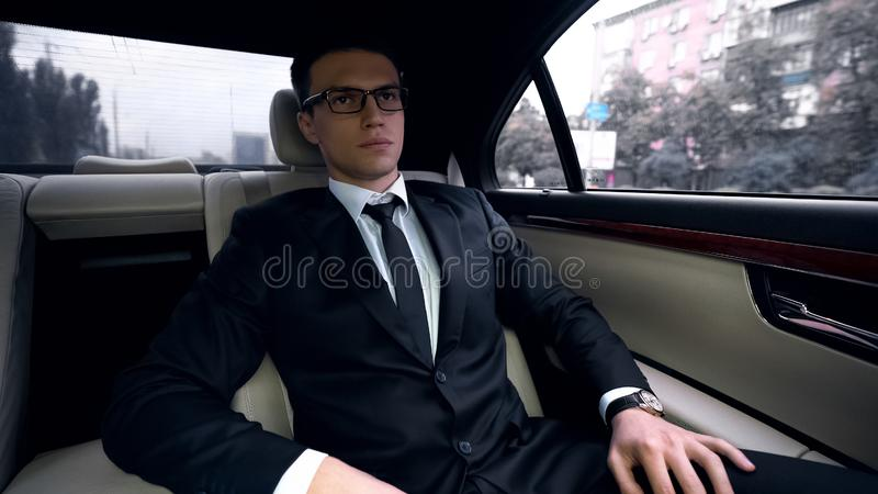 Young successful businessman going to meeting in luxury auto, traffic in city. Stock photo stock images