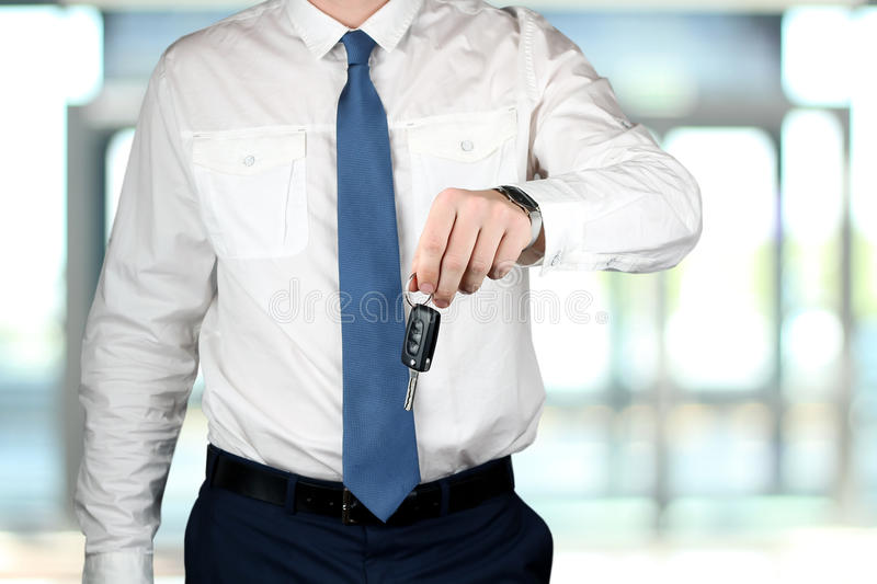 Young successful businessman offering a car key. Young successful businessman offering a car key royalty free stock photo