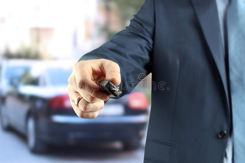 Young successful businessman offering a car key. The young successful businessman offering a car key royalty free stock photos