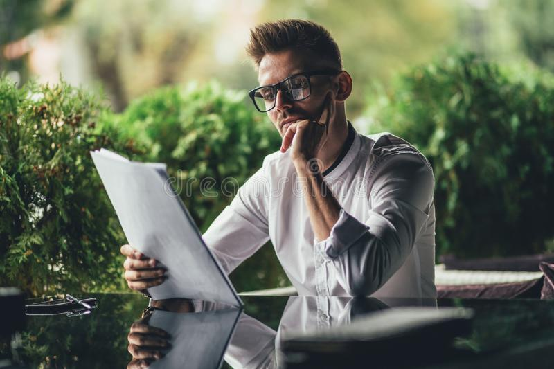 Young successful businessman is reading contract, sitting at table in cafe. Side view stock photography