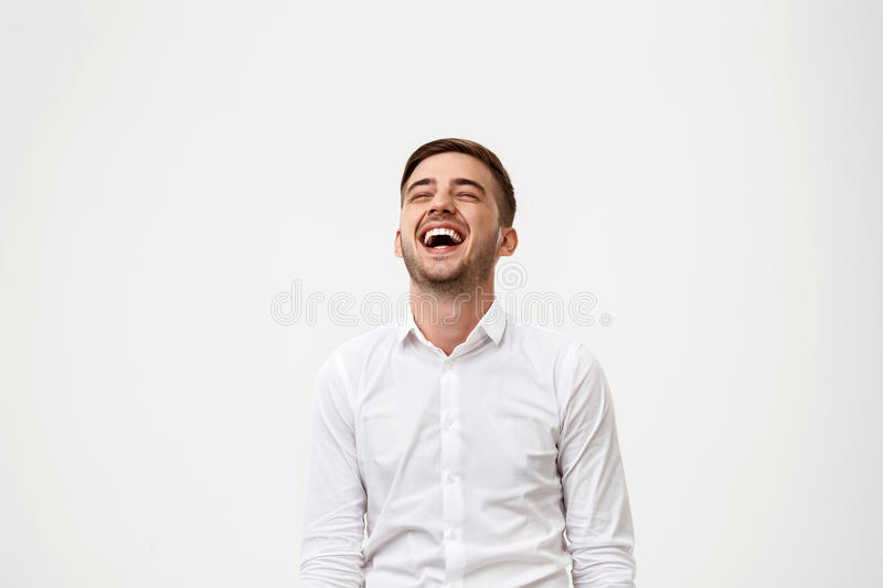 Young successful businessman smiling, laughing over white background. royalty free stock image