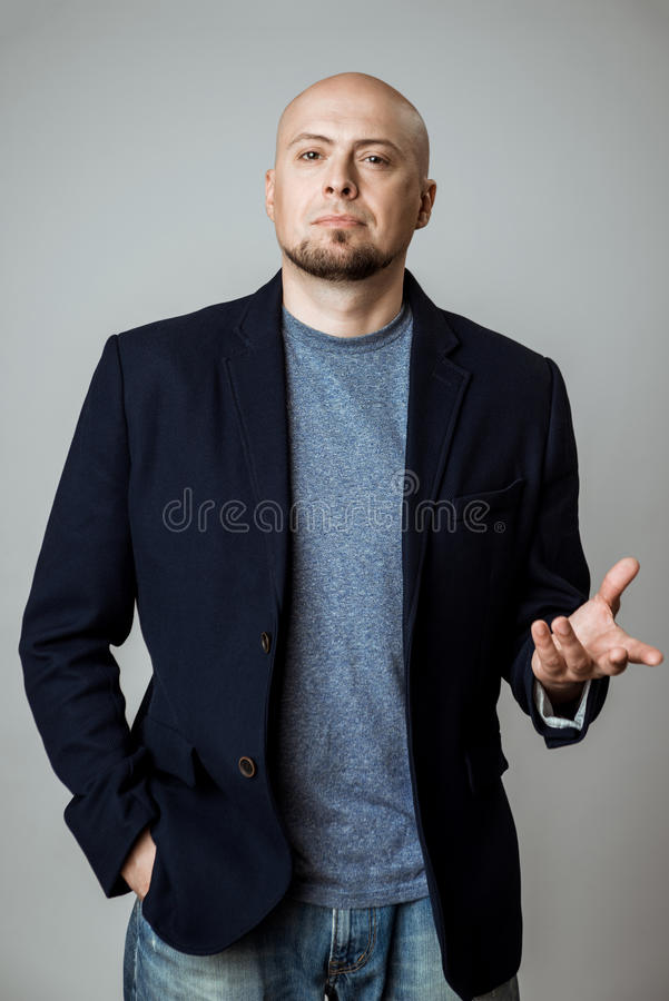Young successful businessman thinking, posing over beige background. stock photo