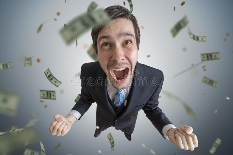 Young successful businessman is a winner. Money are falling from above royalty free stock photos