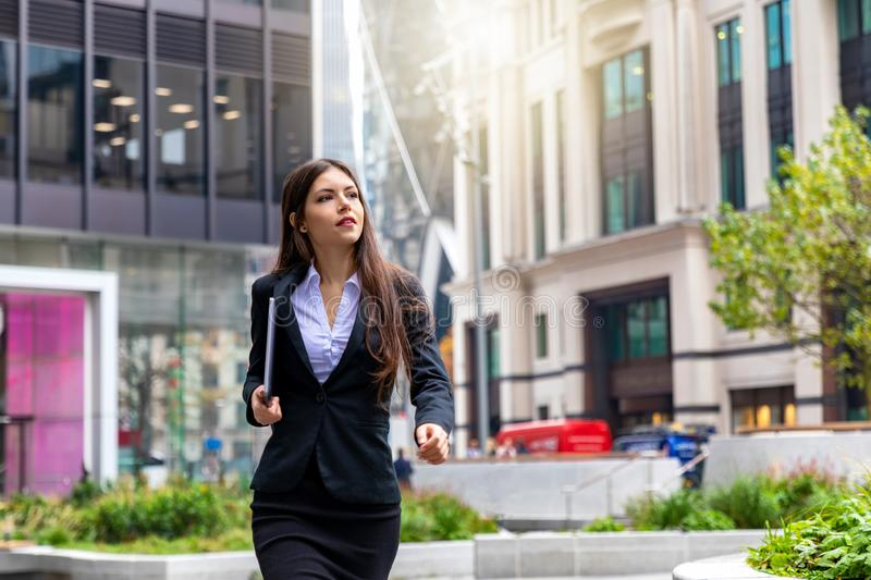 Businesswoman walks outdoors in the City of London, UK. Young and successful businesswoman with a laptop in her hands walks outdoors in the City of London, UK royalty free stock photos