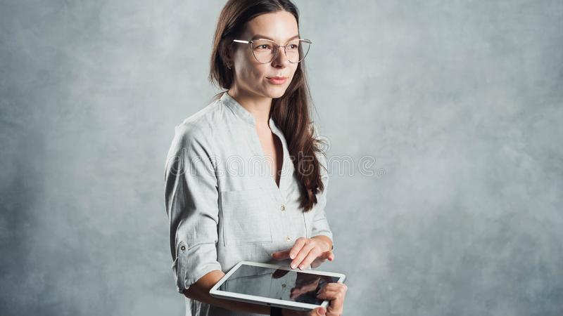 Young successful confident woman in a gray shirt uses a digital tablet for work and Internet access royalty free stock photography