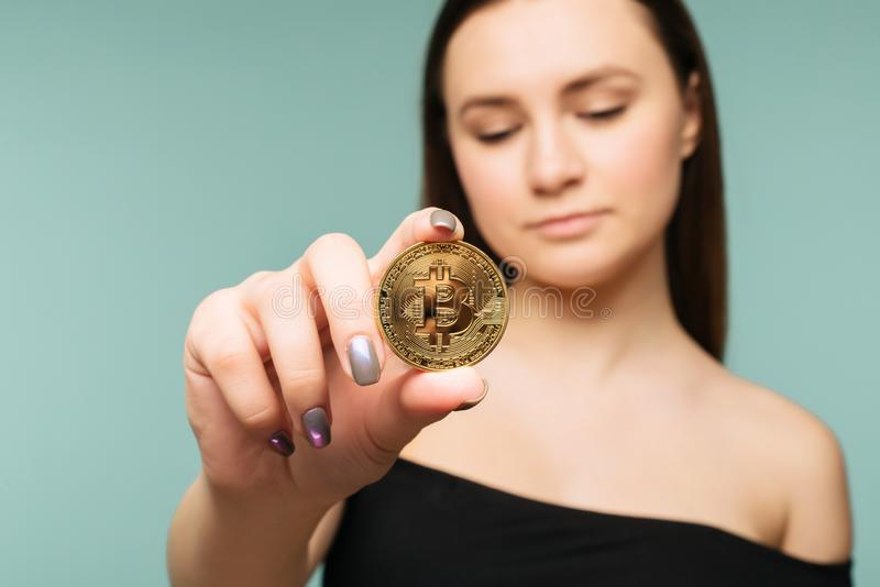 Young successful confident woman holds a gold bitcoin in her hand stock photography