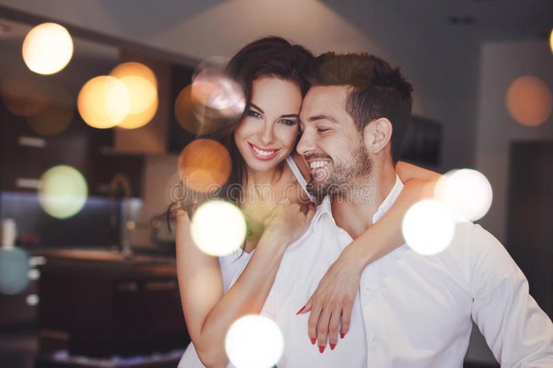 Young successful couple smiling, woman embrace man indoors, boke royalty free stock photos