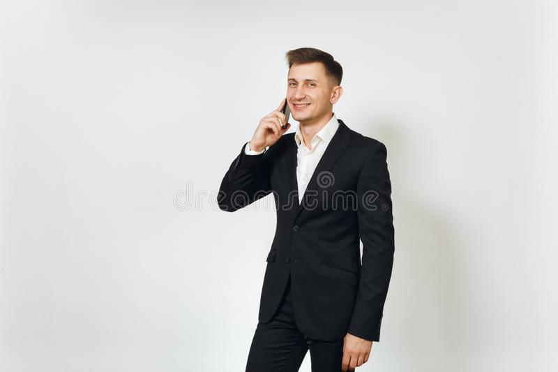 Young successful handsome rich business man in black suit on white background for advertising. stock image