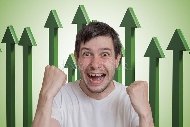 Young successful and happy man and green arrows up in background stock photography