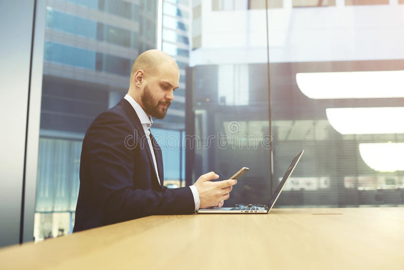 Young successful man manager is reading message on cellphone. Managing director is planning time conducting working meetings by using mobile phone, while is stock images