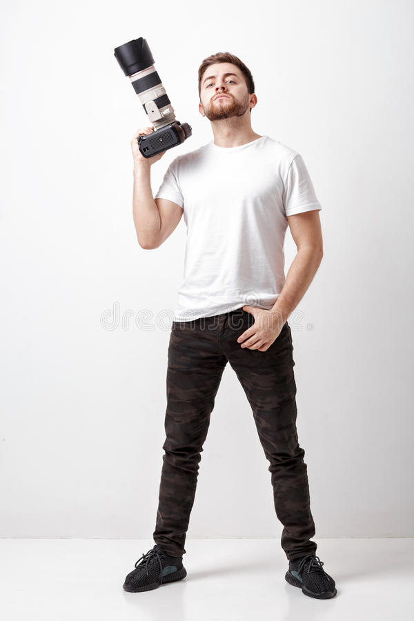 Young successful professional photographer in t-shirt use digita. Young successful professional photographer in white t-shirt use digital camera with a long lens royalty free stock photography