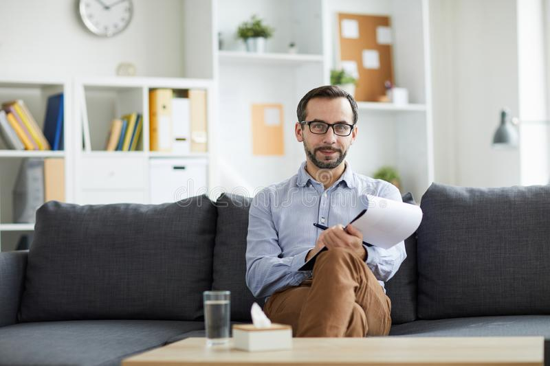 Successful counselor. Young successful pychologist looking at you while sitting on couch in front of camera in his office royalty free stock images