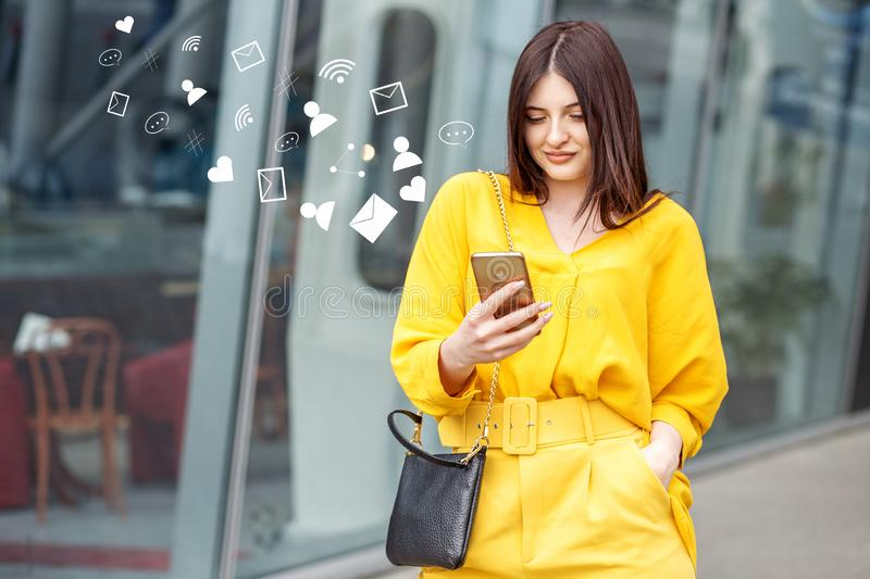 Young successful woman communicates through social networks. Concept for lifestyle, business, technology and fashion stock images