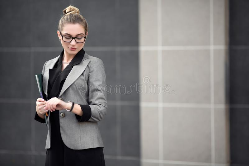 Young successful woman in a strict suit looks at the wristwatch. A woman in the city is holding a file. royalty free stock photography