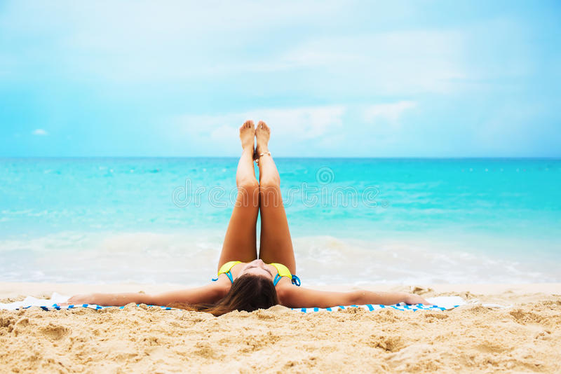 Young Suntan Woman Lying Stretching Up Slender Leg royalty free stock images