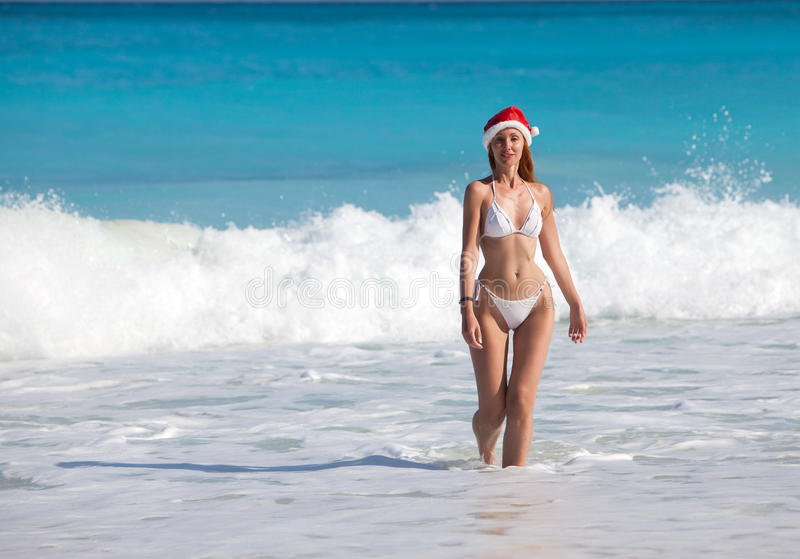 The young suntanned slender woman with a long fair hair in white sexual bikini goes on a peschenny beach against the turquoise oce