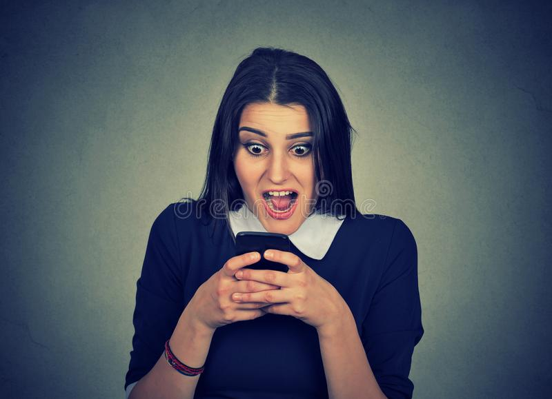 Shocked young woman watching cellphone stock photo