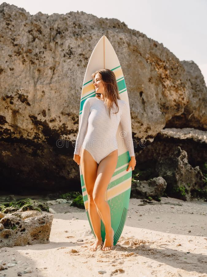 Young surf girl with surfboard poising at beach. Surfer woman standing at beach. royalty free stock image