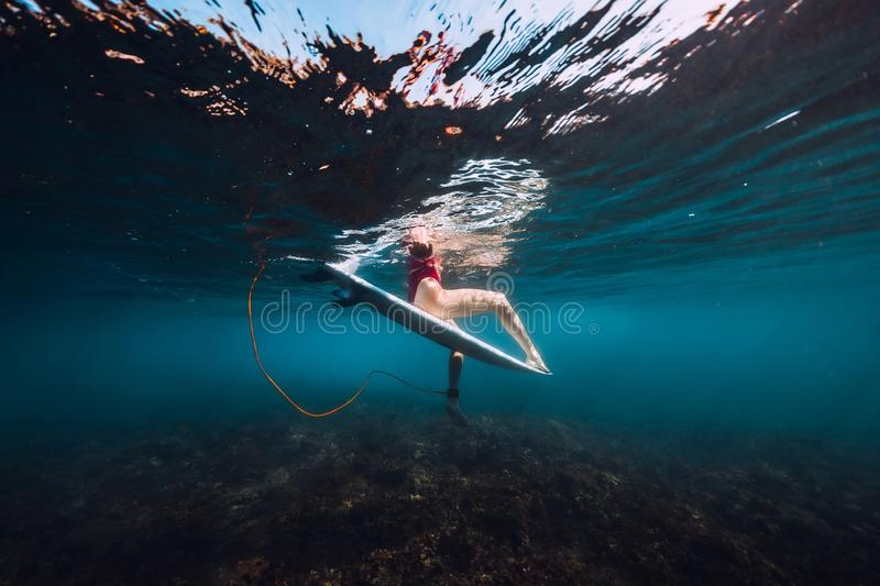 Young surf girl at surfboard underwater in sea. Young surf girl at surfboard underwater in ocean royalty free stock photos