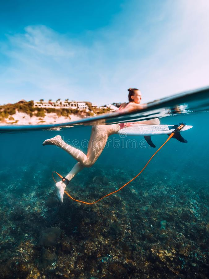 Young surf girl at surfboard underwater in sea. Young surf girl at surfboard underwater in ocean royalty free stock photography