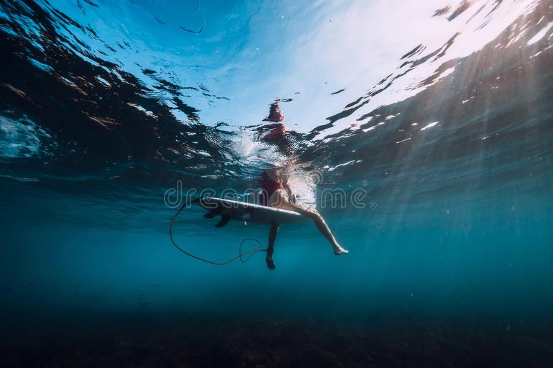 Young surf girl at surfboard underwater in sea. Young surf girl at surfboard underwater in ocean stock image
