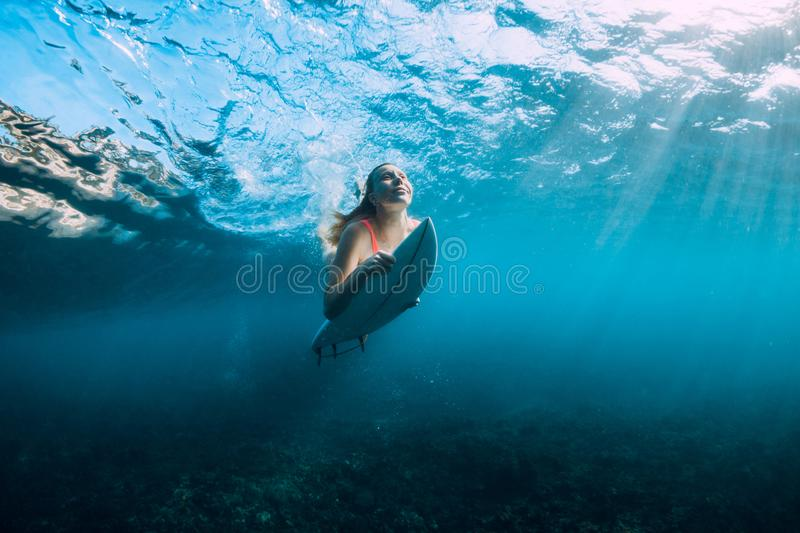 Young surf girl at surfboard underwater in sea. Surfer girl with surfboard dive underwater stock photo