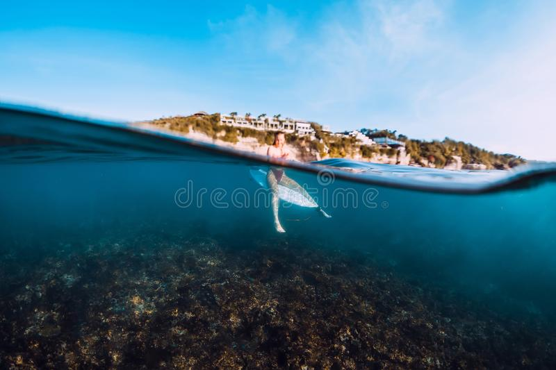 Young surf girl at surfboard underwater in sea. Young surf girl at surfboard underwater in ocean stock photography