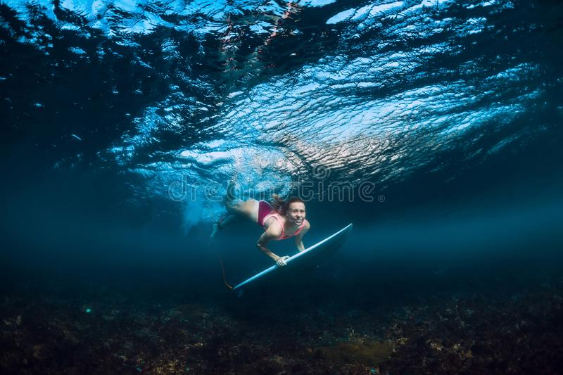 Young surfer woman dive underwater with under wave. Young surfer woman dive underwater with wave stock photo