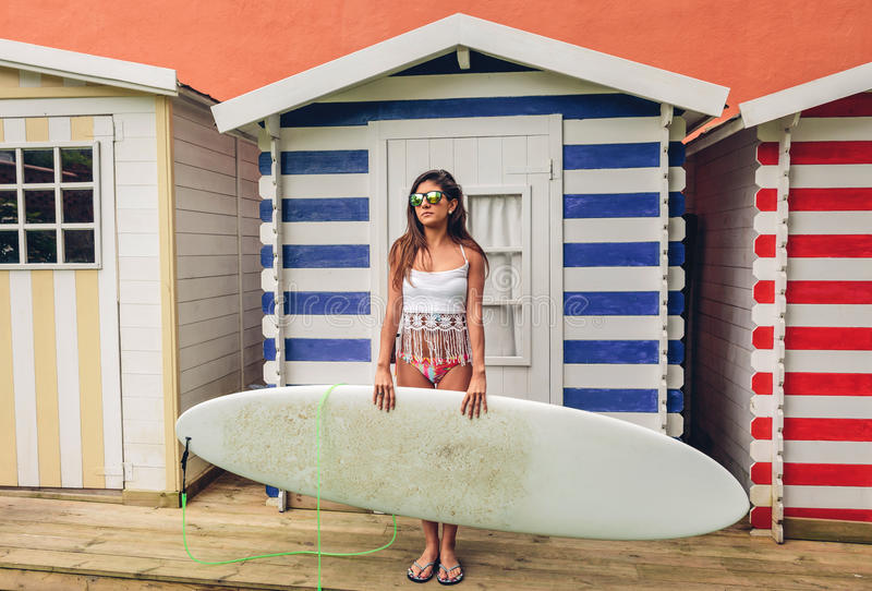 Young surfer woman with top and bikini holding surfboard royalty free stock images