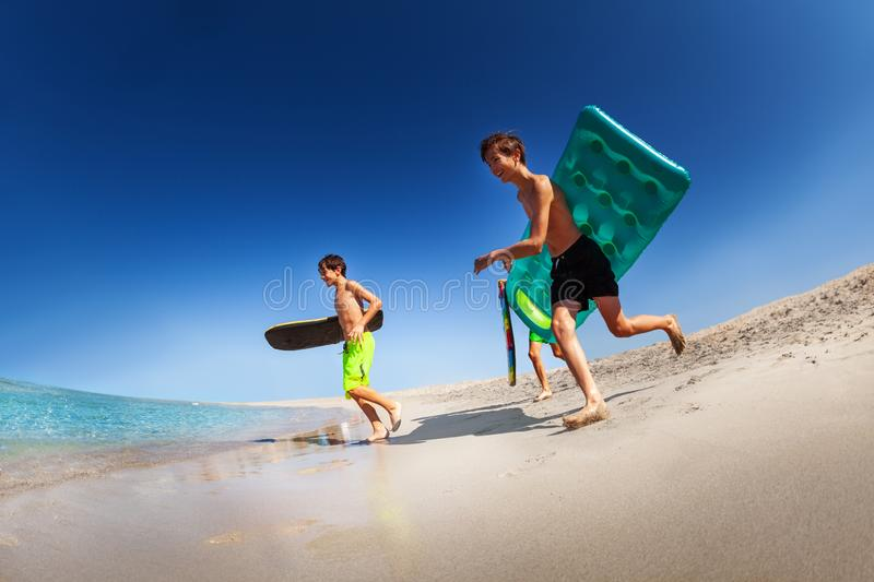 Young surfers running with bodyboards along beach stock photography