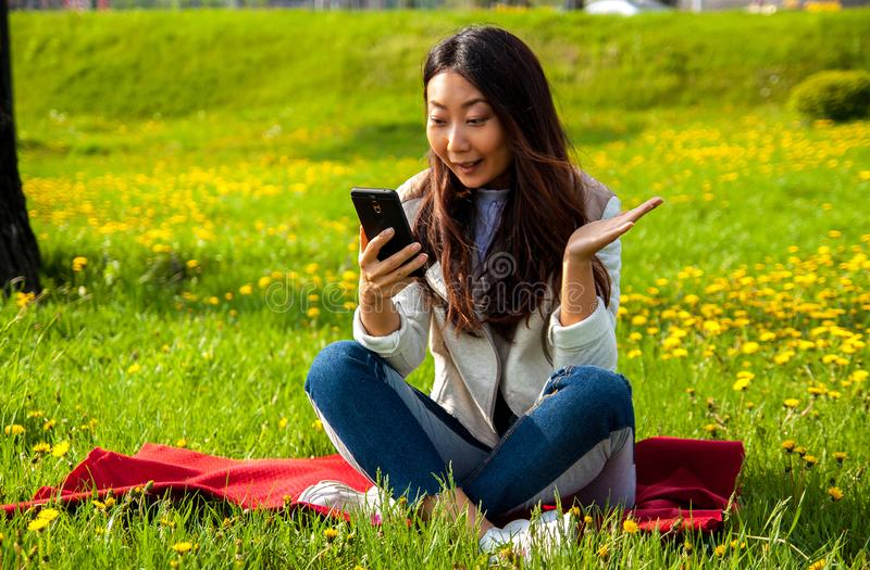 Asian woman calling by phone in summer park on green grass. Young surprised asian woman in park looking at smartphone while sitting on green grass stock image