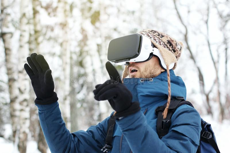 Young surprised bearded man in knitted hat, warm jacket and gloves using virtual reality glasses in winter forest. Future. Technology concept stock image