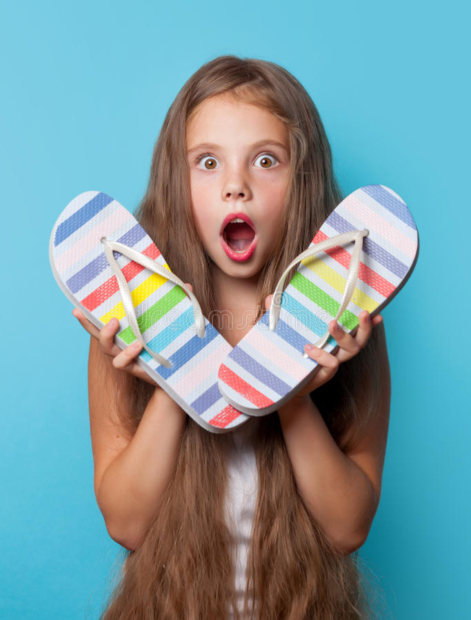 Young surprised girl with flip flops. On blue background royalty free stock images