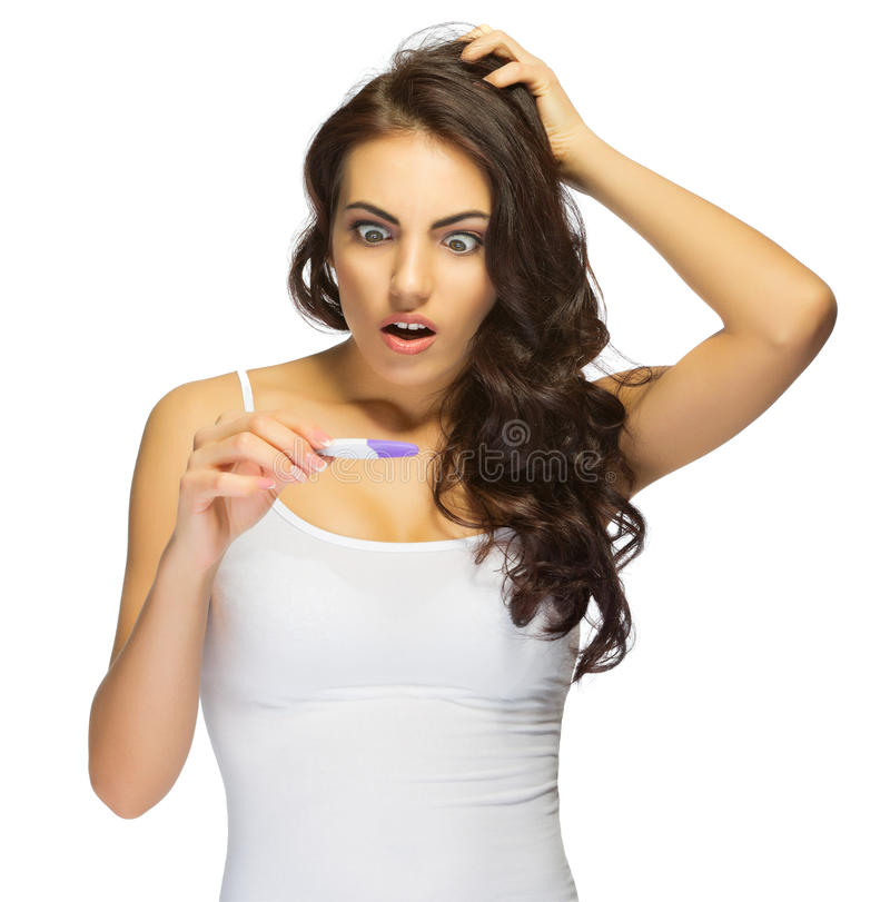 Young surprised girl with pregnancy test stock photo