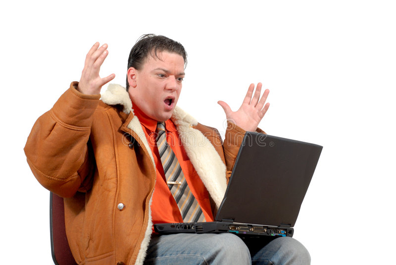 Young surprised looking businessman working on laptop royalty free stock image