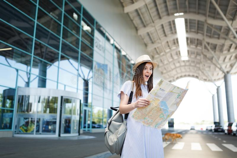 Young surprised traveler tourist woman with backpack holding paper map at international airport. Female passenger. Traveling abroad to travel on weekends royalty free stock photos
