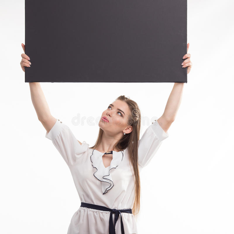 Young surprised woman showing presentation, pointing on placard royalty free stock image
