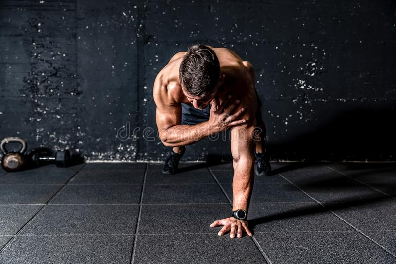Young sweaty strong and fit muscular man push ups workout with touching his shoulder on one hand in the gym on the floor. Gym workout, Young sweaty strong and royalty free stock photos
