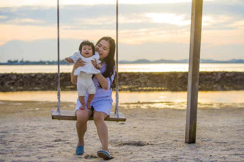 Young sweet and happy Asian Chinese woman holding baby girl swinging together at beach swing on Summer sunset in mother and little royalty free stock photography