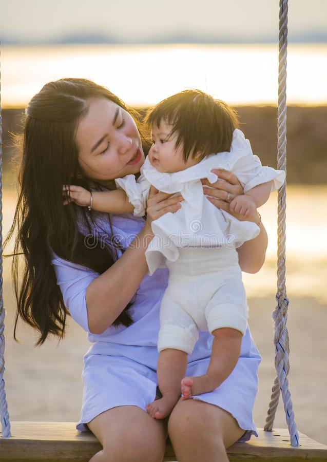 Young sweet and happy Asian Chinese woman holding baby girl swinging together at beach swing on Summer sunset in mother and little stock photo