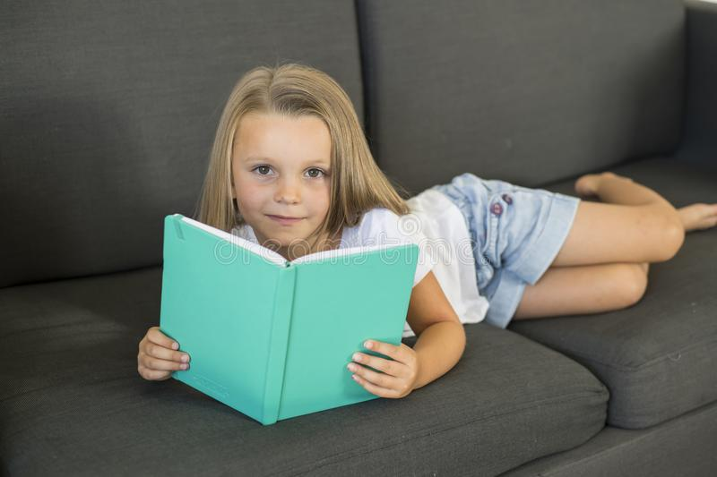 Young sweet and happy little girl 6 or 7 years old lying on home living room sofa couch reading a book quiet and adorable in child. Ren education and lifestyle stock photography