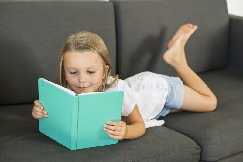 Young sweet and happy little girl 6 or 7 years old lying on home living room sofa couch reading a book quiet and adorable in child. Ren education and lifestyle royalty free stock image