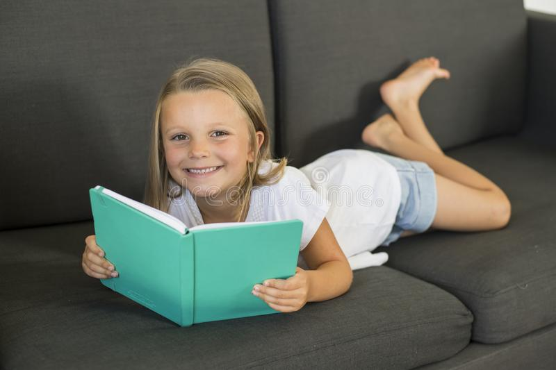 Young sweet and happy little girl 6 or 7 years old lying on home living room sofa couch reading a book quiet and adorable in child. Ren education and lifestyle royalty free stock images